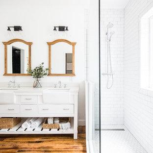 Lantlig inredning av ett vit vitt badrum, med släta luckor, vita skåp, en hörndusch, vit kakel, tunnelbanekakel, vita väggar, mellanmörkt trägolv, ett undermonterad handfat, brunt golv och med dusch som är öppen