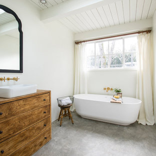 Freestanding bathtub - farmhouse master concrete floor and gray floor freestanding bathtub idea in San Francisco with furniture-like cabinets, medium tone wood cabinets, white walls and a vessel sink