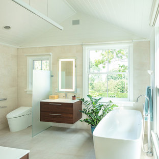 Mid-sized coastal master beige tile and porcelain tile beige floor and porcelain floor bathroom photo in Other with flat-panel cabinets, dark wood cabinets, a wall-mount toilet, white walls, an integrated sink, white countertops, solid surface countertops and a hinged shower door