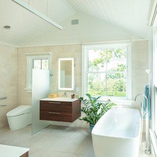 Идея дизайна: главная ванная комната среднего размера в морском стиле с плоскими фасадами, темными деревянными фасадами, отдельно стоящей ванной, инсталляцией, бежевой плиткой, белыми стенами, монолитной раковиной, бежевым полом, белой столешницей, душем без бортиков, керамогранитной плиткой, полом из керамогранита, столешницей из искусственного камня и душем с распашными дверями