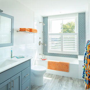 Inspiration for a mid-sized beach style kids' blue tile and subway tile porcelain floor and gray floor bathroom remodel in Other with shaker cabinets, blue cabinets, white walls, an integrated sink, white countertops, a one-piece toilet and solid surface countertops