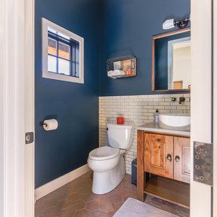 На фото: ванная комната среднего размера в стиле кантри с фасадами с выступающей филенкой, искусственно-состаренными фасадами, унитазом-моноблоком, белой плиткой, плиткой кабанчик, синими стенами, полом из керамогранита, душевой кабиной, настольной раковиной, столешницей из искусственного кварца, оранжевым полом и белой столешницей с
