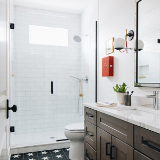 Mid-sized transitional kids' black tile and terra-cotta tile limestone floor, gray floor and double-sink bathroom photo in Chicago with shaker cabinets, white walls, an undermount sink, white countertops, gray cabinets, a two-piece toilet, quartz countertops and a built-in vanity