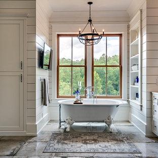 Imagen de cuarto de baño principal, campestre, grande, con armarios estilo shaker, puertas de armario grises, bañera con patas, paredes blancas, suelo gris, encimeras blancas, ducha esquinera, suelo de cemento, lavabo bajoencimera y ducha con puerta con bisagras