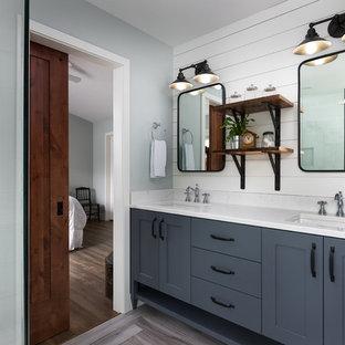 Imagen de cuarto de baño principal, de estilo de casa de campo, de tamaño medio, con armarios estilo shaker, puertas de armario grises, lavabo bajoencimera, encimera de cuarzo compacto, suelo gris y paredes blancas