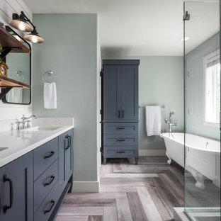 Cette photo montre une salle de bain principale nature de taille moyenne avec un placard à porte shaker, des portes de placard grises, une baignoire sur pieds, une douche d'angle, un lavabo encastré, un plan de toilette en quartz modifié, un sol gris, une cabine de douche à porte battante et un mur vert.