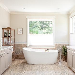 Klassisk inredning av ett stort en-suite badrum, med skåp i shakerstil, grå skåp, ett fristående badkar, en dusch i en alkov, en toalettstol med separat cisternkåpa, flerfärgad kakel, brun kakel, travertinkakel, grå väggar, travertin golv, ett undermonterad handfat, marmorbänkskiva, dusch med gångjärnsdörr och brunt golv