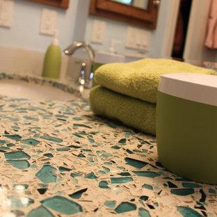 Imagen de cuarto de baño tradicional renovado, pequeño, con lavabo bajoencimera, armarios con paneles empotrados, puertas de armario de madera oscura, encimera de vidrio reciclado, bañera empotrada, combinación de ducha y bañera, sanitario de dos piezas, baldosas y/o azulejos azules, paredes azules y suelo de baldosas de porcelana