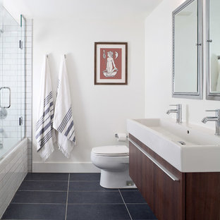 Example of a large trendy master white tile and subway tile porcelain tile and gray floor bathroom design in Denver with flat-panel cabinets, dark wood cabinets, white walls, a trough sink and a hinged shower door