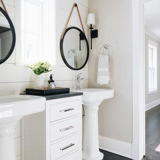 Bild på ett lantligt grå grått badrum, med släta luckor, vita skåp, grå väggar, ett piedestal handfat och svart golv