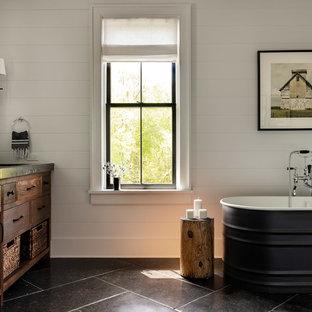 Diseño de cuarto de baño principal, de estilo de casa de campo, grande, con armarios con paneles lisos, puertas de armario marrones, bañera exenta, baldosas y/o azulejos blancos, paredes blancas, lavabo bajoencimera, encimera de cemento, suelo negro, encimeras negras y suelo de pizarra