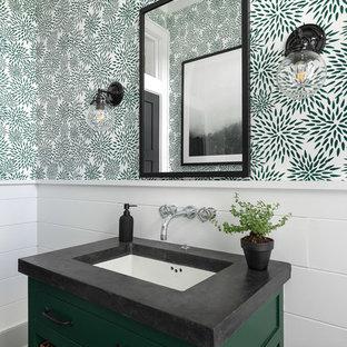Modelo de cuarto de baño de estilo de casa de campo, de tamaño medio, con armarios con paneles lisos, puertas de armario verdes, baldosas y/o azulejos blancos, paredes blancas, suelo de pizarra, lavabo bajoencimera, encimera de cemento, suelo negro y encimeras negras