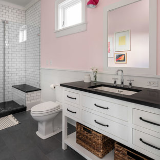 Example of a large farmhouse subway tile and white tile slate floor and gray floor bathroom design in New York with flat-panel cabinets, white cabinets, a two-piece toilet, an undermount sink, black countertops, pink walls and a hinged shower door