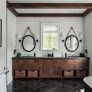 Источник вдохновения для домашнего уюта: большая главная ванная комната в стиле кантри с плоскими фасадами, отдельно стоящей ванной, белой плиткой, плиткой кабанчик, белыми стенами, полом из сланца, врезной раковиной, столешницей из бетона, черным полом, черной столешницей и темными деревянными фасадами