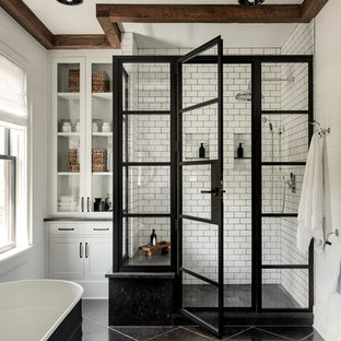 Photo of a large country master bathroom in New York with a corner shower, white tile, subway tile, white walls, slate floors, black floor, a hinged shower door and a freestanding tub.