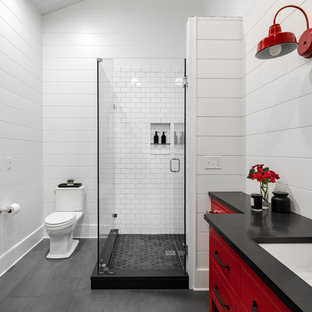 Example of a large cottage white tile and subway tile slate floor and gray floor corner shower design in New York with flat-panel cabinets, red cabinets, a two-piece toilet, white walls, an undermount sink, concrete countertops, black countertops and a hinged shower door