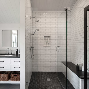 Inspiration for a large cottage white tile and subway tile slate floor and black floor doorless shower remodel in New York with flat-panel cabinets, white cabinets, white walls, an undermount sink, concrete countertops, a hinged shower door and black countertops