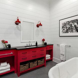 Diseño de cuarto de baño campestre, grande, con armarios con paneles lisos, puertas de armario rojas, bañera exenta, baldosas y/o azulejos blancos, paredes blancas, suelo de pizarra, lavabo bajoencimera, encimera de cemento, suelo gris y encimeras negras