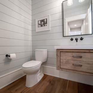 This is an example of a traditional bathroom in Chicago with freestanding cabinets, medium wood cabinets, a two-piece toilet, grey walls, medium hardwood flooring, brown floors and white worktops.