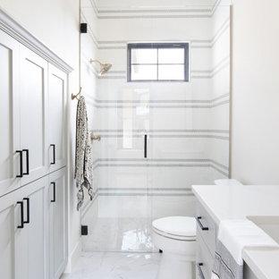 Landhausstil Badezimmer mit Schrankfronten mit vertiefter Füllung, grauen Schränken, Duschnische, weißen Fliesen, Mosaikfliesen, weißer Wandfarbe, Unterbauwaschbecken, weißem Boden, Falttür-Duschabtrennung und weißer Waschtischplatte in Austin