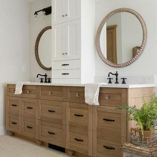 Modelo de cuarto de baño principal, minimalista, grande, con armarios con rebordes decorativos, puertas de armario de madera clara, bañera exenta, ducha abierta, sanitario de una pieza, paredes beige, suelo de madera pintada, lavabo encastrado, suelo blanco, ducha abierta y encimeras blancas