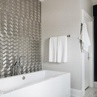 На фото: главные ванные комнаты среднего размера в стиле модернизм с плоскими фасадами, белыми фасадами, отдельно стоящей ванной, душем в нише, инсталляцией, серой плиткой, металлической плиткой, серыми стенами, полом из керамогранита, настольной раковиной, столешницей из искусственного кварца, серым полом, душем с распашными дверями и белой столешницей