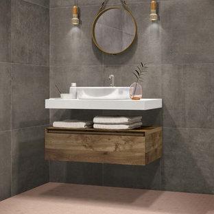 Foto de cuarto de baño con ducha, minimalista, con armarios con paneles lisos, puertas de armario de madera oscura, baldosas y/o azulejos grises, baldosas y/o azulejos de porcelana, paredes grises, suelo de baldosas de porcelana, encimeras blancas, lavabo sobreencimera y suelo rosa