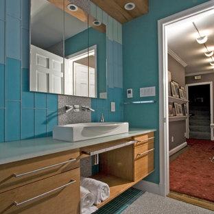 Immagine di una grande stanza da bagno con doccia contemporanea con lavabo a bacinella, ante lisce, ante in legno chiaro, piastrelle blu, piastrelle di vetro, top in quarzo composito, doccia ad angolo, pareti blu e pavimento in gres porcellanato