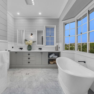 This is an example of a beach style master bathroom in Brisbane with shaker cabinets, grey cabinets, a freestanding tub, white tile, subway tile, grey walls, grey floor and white benchtops.
