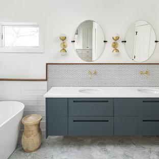 На фото: главная ванная комната в современном стиле с плоскими фасадами, отдельно стоящей ванной, белой плиткой, мраморным полом, врезной раковиной, серым полом и желтой столешницей с