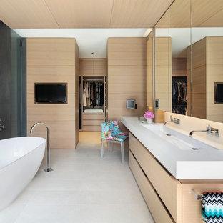 Modelo de cuarto de baño principal, minimalista, con armarios con paneles lisos, puertas de armario de madera clara, bañera exenta, paredes grises, lavabo de seno grande y suelo blanco