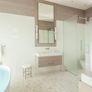 Esempio di una grande stanza da bagno padronale minimal con vasca freestanding, piastrelle beige, lavabo sospeso, WC a due pezzi, piastrelle a mosaico, pareti beige, ante lisce, ante in legno chiaro, doccia alcova, pavimento con piastrelle a mosaico, top in superficie solida, pavimento beige, porta doccia scorrevole e top bianco