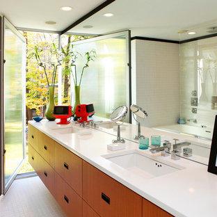 Modelo de cuarto de baño moderno con lavabo bajoencimera, armarios con paneles lisos, puertas de armario de madera oscura y combinación de ducha y bañera