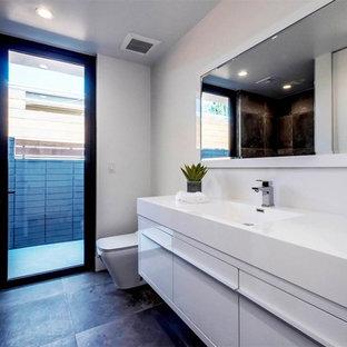 Diseño de cuarto de baño principal, actual, de tamaño medio, sin sin inodoro, con armarios con paneles lisos, puertas de armario blancas, sanitario de una pieza, paredes blancas, suelo de cemento, lavabo integrado, encimera de acrílico, suelo gris y ducha abierta