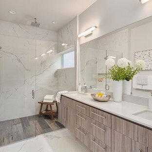 Modern inredning av ett vit vitt badrum, med släta luckor, grå skåp, en dusch i en alkov, vita väggar, ett undermonterad handfat, vitt golv och dusch med gångjärnsdörr