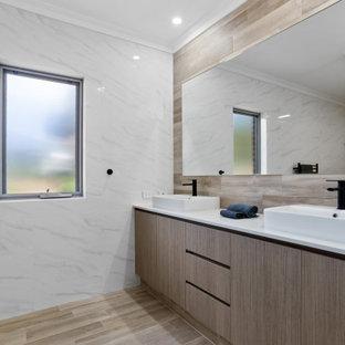 Diseño de cuarto de baño industrial con armarios con paneles lisos, puertas de armario de madera oscura, baldosas y/o azulejos beige, suelo de baldosas de cerámica, lavabo encastrado, encimera de cuarzo compacto, suelo beige y encimeras blancas