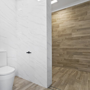 Ispirazione per una stanza da bagno industriale con ante lisce, ante in legno scuro, piastrelle beige, piastrelle effetto legno, pavimento con piastrelle in ceramica, lavabo da incasso, top in quarzo composito, pavimento beige e top bianco