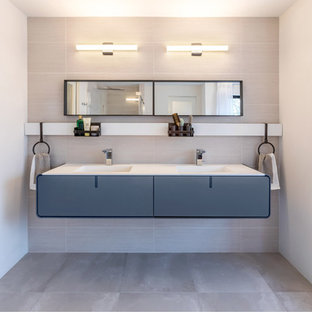 Example of a trendy master porcelain tile and gray tile porcelain floor and gray floor bathroom design in Baltimore with flat-panel cabinets, white walls, an integrated sink, solid surface countertops, white countertops and gray cabinets