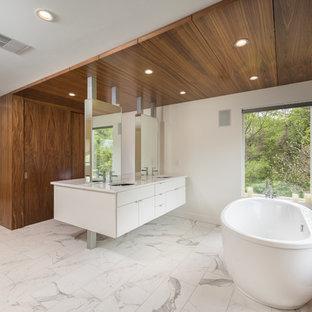 Foto di una grande stanza da bagno padronale minimalista con ante lisce, ante bianche, vasca freestanding, pareti bianche, pavimento in marmo, lavabo sottopiano, top in laminato e pavimento bianco