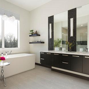 Ispirazione per una stanza da bagno padronale design con ante lisce, ante nere, doccia alcova, piastrelle nere, piastrelle a listelli, pareti beige, lavabo sottopiano, pavimento grigio, porta doccia a battente e top beige
