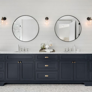 Пример оригинального дизайна: главная ванная комната в стиле кантри с фасадами с декоративным кантом, черными фасадами, отдельно стоящей ванной, белыми стенами, врезной раковиной, серым полом и белой столешницей