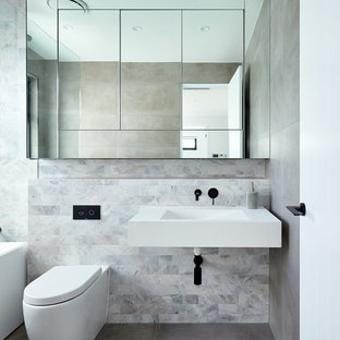 Photo of a contemporary bathroom in Sydney with an alcove tub, gray tile, an integrated sink, grey floor and white benchtops.