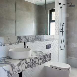 This is an example of a contemporary bathroom in Sydney with white tile, a vessel sink, grey floor and grey benchtops.