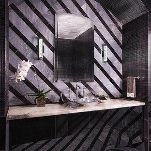 Foto de cuarto de baño contemporáneo, de tamaño medio, con lavabo sobreencimera, armarios tipo vitrina, puertas de armario negras, encimera de ónix, sanitario de pared, baldosas y/o azulejos negros, baldosas y/o azulejos de piedra, paredes grises y suelo de mármol