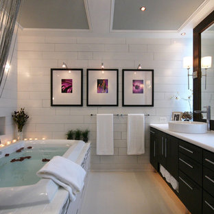 Example of a mid-sized trendy master subway tile and white tile drop-in bathtub design in Charlotte with flat-panel cabinets, dark wood cabinets, laminate countertops and a vessel sink