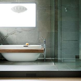 Réalisation d'une très grande salle de bain principale minimaliste avec un placard à porte plane, des portes de placard blanches, une baignoire indépendante, une douche à l'italienne, un carrelage gris, des carreaux de porcelaine, un sol en carrelage de porcelaine, un plan de toilette en quartz modifié, aucune cabine, un plan de toilette gris et un sol gris.