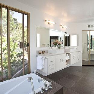 Ejemplo de cuarto de baño moderno con lavabo sobreencimera, armarios con paneles lisos, puertas de armario blancas, bañera esquinera, paredes blancas, suelo de baldosas de porcelana y baldosas y/o azulejos grises
