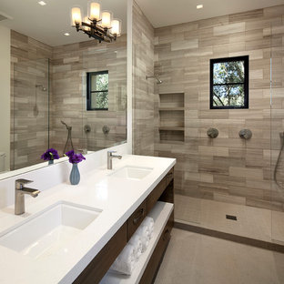 Modelo de cuarto de baño principal, mediterráneo, grande, con lavabo bajoencimera, armarios con paneles lisos, puertas de armario de madera en tonos medios, ducha empotrada, baldosas y/o azulejos grises, baldosas y/o azulejos de piedra, paredes blancas, suelo de baldosas de porcelana y encimera de acrílico