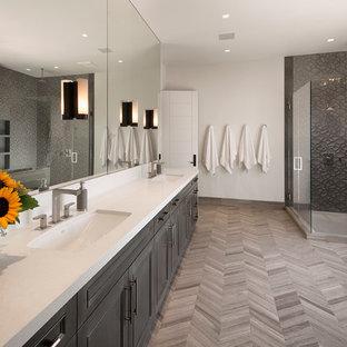 Inredning av ett modernt stort en-suite badrum, med ett undermonterad handfat, luckor med infälld panel, grå skåp, en hörndusch, grå kakel, vita väggar, ljust trägolv och bänkskiva i akrylsten