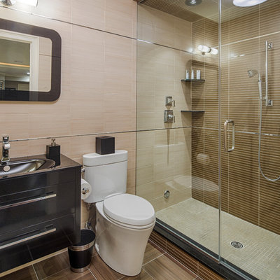Inspiration for a mid-sized contemporary 3/4 brown tile and porcelain tile porcelain tile and brown floor alcove shower remodel in New York with an integrated sink, a two-piece toilet, flat-panel cabinets, black cabinets, solid surface countertops, a hinged shower door and black countertops